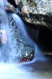 在缎软的河溪包围的岩石的抽象美丽的景色 图库摄影