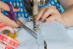 在缝纫机的妇女手 在缝纫机的裁缝工作 爱好缝合的织品作为一个小企业概念 免版税库存照片