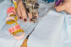 在缝纫机的妇女手 在缝纫机的裁缝工作 爱好缝合的织品作为一个小企业概念 库存图片