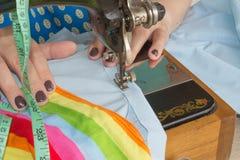 在缝纫机的妇女手 在缝纫机的裁缝工作 爱好缝合的织品作为一个小企业概念 库存照片