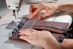 在缝纫机的妇女的手 免版税库存照片