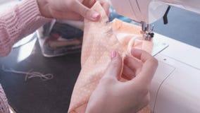 在缝纫机的妇女缝合的细节 显示并且解释如何缝合 特写镜头手 影视素材