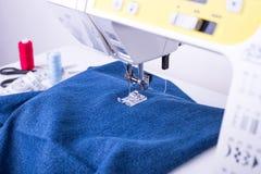 在缝纫机的牛仔裤织品在被缝合的脚下 免版税库存图片