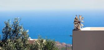 在缩样的风车在一个大阳台的基石有海视图 免版税图库摄影