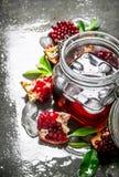 在罐子与冰和切片的石榴汁与叶子 图库摄影