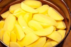 在罐或平底锅的未加工的被剥皮的土豆。健康食物。 库存图片
