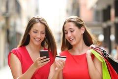 在网上买与信用卡和手机的顾客 免版税库存照片