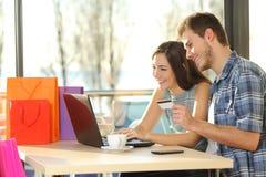 在网上买与购物袋的夫妇 免版税库存图片