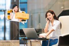 在网上亚洲女孩商店使用与交付小包箱子的女性小企业主的电话 互联网购物生活方式 免版税库存照片