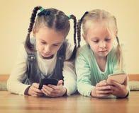 在网上使用与电话的女孩 免版税图库摄影