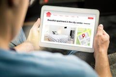 在网上供以人员查寻公寓和房子与移动设备 库存照片