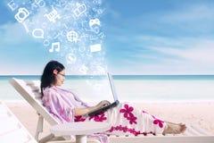 在网上冲浪使用膝上型计算机的亚裔女性在海滩 免版税库存图片