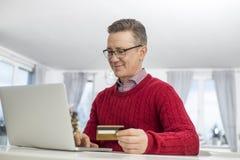 在网上在圣诞节期间,使用信用卡和膝上型计算机的成熟人购物 免版税库存照片