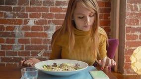在网上坐在表承办酒席自助餐食物餐馆,女孩使用聪明的电话网络通信的咖啡休息的妇女 影视素材