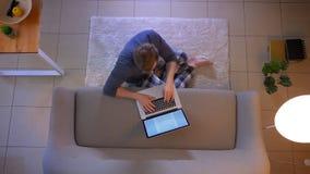 在网上学习和写杂文的年轻便服男性特写镜头顶面射击在膝上型计算机坐地板 股票视频