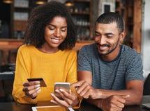 在网上年轻夫妇购物通过手机 库存图片