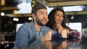 在网上庆祝队胜利,观看的体育竞赛的男性和女性爱好者 影视素材