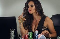 在网上打扑克的年轻肉欲的妇女 免版税库存图片