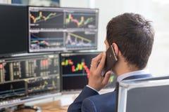 在网上换的屏幕和的股票经纪人肩膀视图  免版税库存照片
