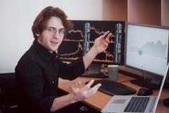在网上换股票的商人 看图表、索引和数字在多个屏幕上的股票经纪人 免版税图库摄影