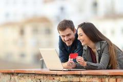 在网上支付与信用卡和膝上型计算机的愉快的夫妇 库存图片