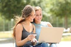 在网上支付与膝上型计算机和信用卡的朋友 库存照片