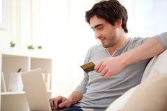 在网上支付与在沙发的信用卡的年轻轻松的人 免版税库存图片
