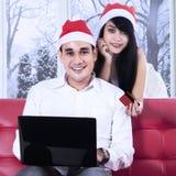 在网上支付圣诞老人的帽子的微笑的夫妇 免版税库存照片