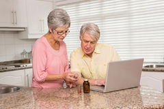 在网上查寻疗程的资深夫妇 免版税图库摄影