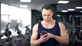 在网上检查在智能手机的运动员健身应用,个人节目 库存图片