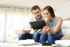 在网上检查银行帐户的担心的夫妇 免版税库存图片