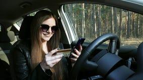 在网上汽车举行信用卡和购物的妇女 股票视频