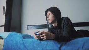 在网上电子游戏吸收的年轻男孩青少年和控制杆人cybersport戴头巾毛线衣 敞篷的男孩少年 影视素材