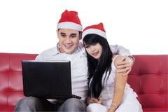 在网上西班牙夫妇购买与膝上型计算机 图库摄影