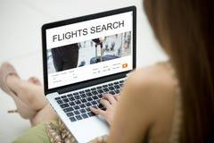 在网上计划往返飞行的女孩使用膝上型计算机 免版税库存照片