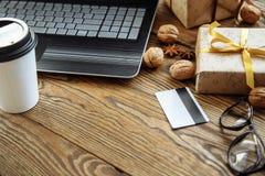 在网上购物与信用卡在圣诞节假日 有礼物的膝上型计算机在木桌上 免版税图库摄影