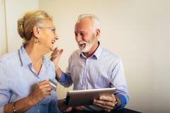 在网上购物与片剂和信用卡的资深夫妇 库存照片