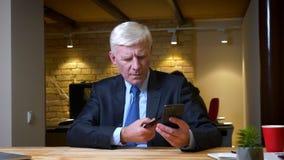 在网上购物使用手机和信用卡的老白种人商人特写镜头射击户内在办公室  股票录像