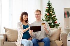 在网上购物在圣诞节的人和怀孕的妻子 图库摄影
