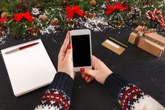 在网上购物在智能手机的圣诞节的妇女 免版税库存照片