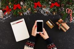 在网上购物在智能手机的圣诞节的妇女 免版税库存图片