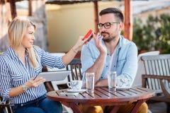 在网上购物愉快的年轻的夫妇坐在咖啡馆和 图库摄影
