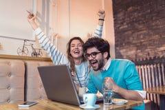 在网上购物愉快的年轻的夫妇坐在咖啡馆和 免版税库存照片