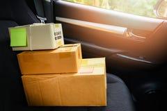 在网上购物电子商务的交付和命令概念/运输的购物的网上纸板箱在汽车座位 免版税库存图片