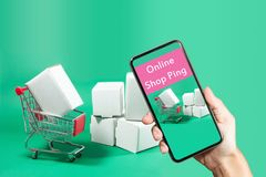 在网上购物的概念:拿着购物的w的手巧妙的电话 免版税库存照片