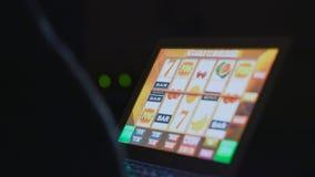 在网上赌博娱乐场老虎机前面的赌博的上瘾的人在附近的便携式计算机上 免版税图库摄影