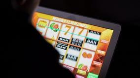 在网上赌博娱乐场老虎机前面的赌博的上瘾的人在附近的便携式计算机上 免版税库存照片