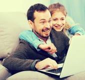 在网上预定的父亲和的女儿 免版税图库摄影