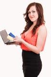 在网上购物与信用卡和膝上型计算机的愉快的少妇 免版税库存图片