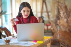 在网上购物与她的信用卡和a的逗人喜爱的少妇 免版税库存照片